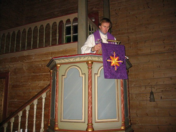 vicar fastening the hanging for the pulpit